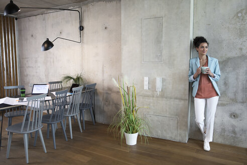 Smiling businesswoman holding coffee mug at concrete wall in a loft - FKF03212