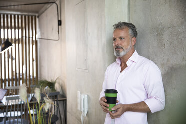 Smiling businessman holding coffee mug at concrete wall in a loft - FKF03215