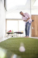 Happy casual businessman playing golf on artificial turf in a loft - FKF03221
