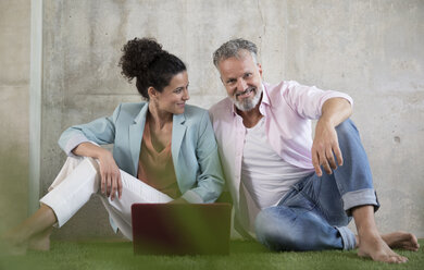 Casual businessman and businesswoman sitting on artificial turf in a loft sharing laptop - FKF03224