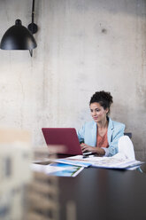 Businesswoman sitting at table in a loft using laptop - FKF03236