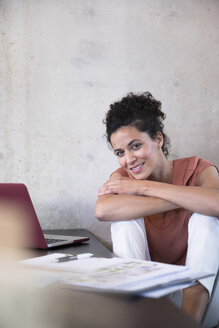 Portrait of smiling businesswoman sitting at table with documents and laptop - FKF03239
