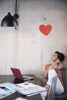 Businesswoman sitting at table in a loft under a heart on concrete wall - FKF03242