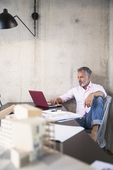 Businessman in a loft using laptop with documents and architectural model on table - FKF03245