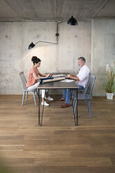 Businessman and businesswoman working at table in a loft - FKF03248
