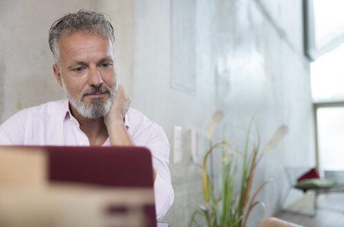 Businessman in a loft using laptop - FKF03251
