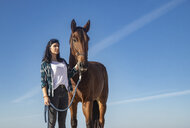 Woman with horse under blue sky - KBF00371
