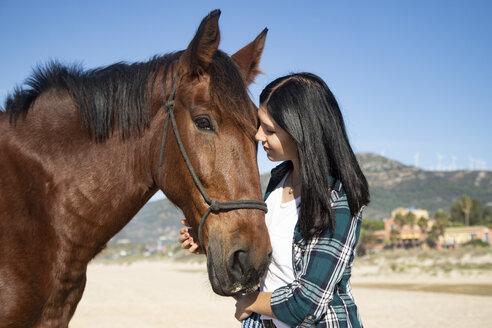 Spain, Tarifa, woman with horse on the beach - KBF00374