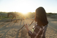 Spain, Tarifa, woman leading horse on riding ring at sunset - KBF00386