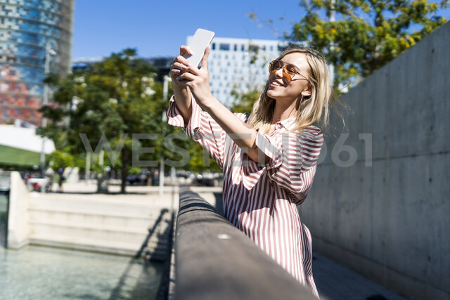Spain, Barcelona, smiling young woman taking selfie with cell phone - GIOF05454 - Giorgio Fochesato/Westend61