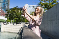 Spain, Barcelona, smiling young woman taking selfie with cell phone - GIOF05454