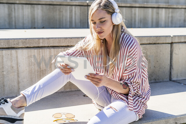 Portrait of blond young woman sitting on stairs outdoors using digital tablet and headphones - GIOF05460
