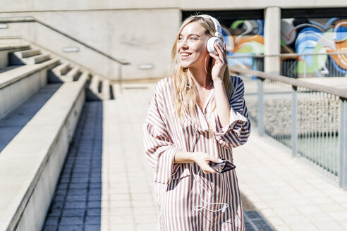 Spain, Barcelona, portrait of smiling blond woman using smartphone and headphones outdoors - GIOF05463