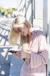 Blond young woman using smartphone outdoors - GIOF05469