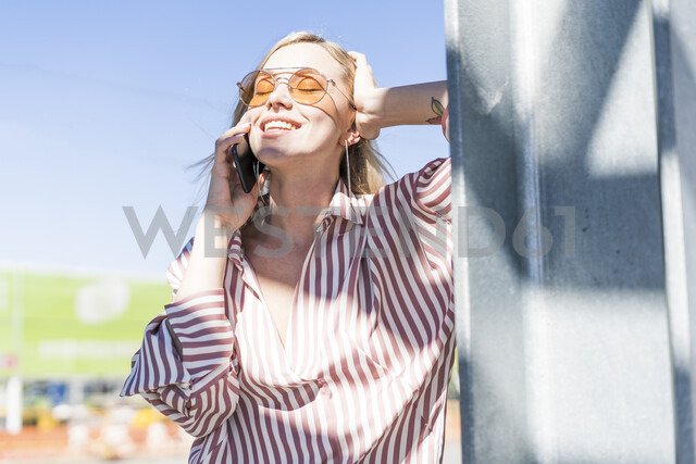 Portrait of smiling young woman on the phone enjoying sunlight - GIOF05472 - Giorgio Fochesato/Westend61