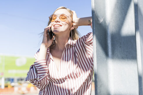 Portrait of smiling young woman on the phone enjoying sunlight - GIOF05472