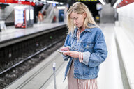 Spain, Barcelona, young blond woman standing at underground station platform looking at cell phone - GIOF05475