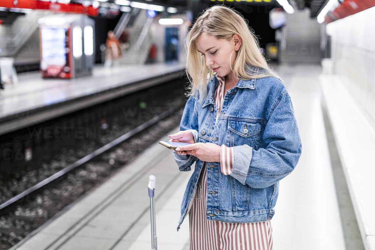Spain, Barcelona, young blond woman standing at underground station platform looking at cell phone - GIOF05475 - Giorgio Fochesato/Westend61