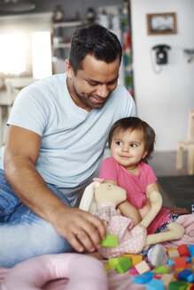 Smiling father and baby girl playing with building blocks at home - ABIF01081