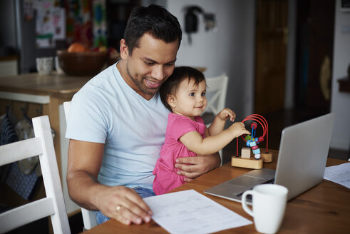 Father with baby girl using laptop on table at home - ABIF01084