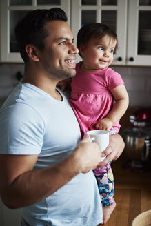 Smiling father holding baby girl in kitchen at home - ABIF01090