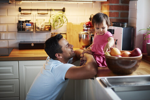 Smiling father looking at baby girl sitting on counter in kitchen at home - ABIF01093