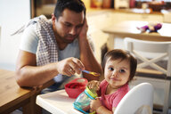 Portrait of baby girl sitting in high chair at home with annoyed father in background - ABIF01099