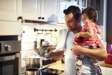 Father preparing meal and holding baby girl in kitchen at home - ABIF01102