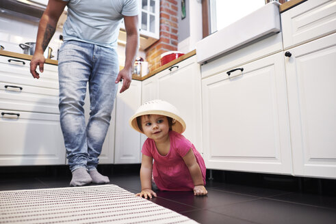 Playful baby girl crawling on the floor in kitchen - ABIF01105