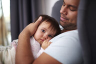 Affectionate father hugging his baby daughter at home - ABIF01108