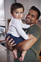Portrait of smiling father holding baby girl at home - ABIF01117