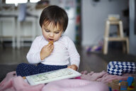 Baby girl sitting on the floor at home eating a cookie and using tablet - ABIF01123