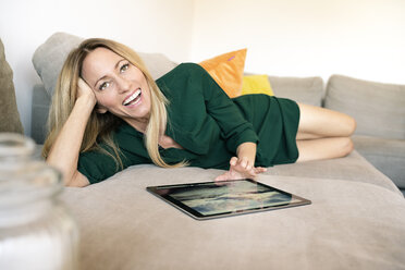 Portrait of laughing woman with digital tablet relaxing on the couch at home - DMOF00080