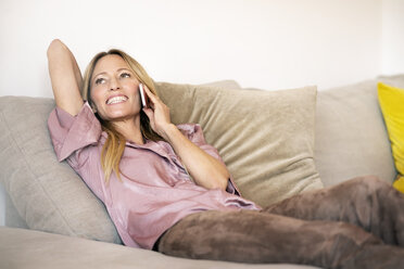 Portrait of woman on the phone relaxing on the couch at home - DMOF00083