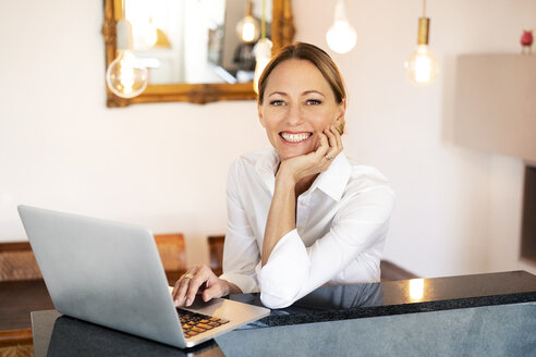 Portrait of smiling businesswoman with laptop at home office - DMOF00089