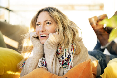 Portrait of smiling blond mature woman relaxing in winter garden - DMOF00092