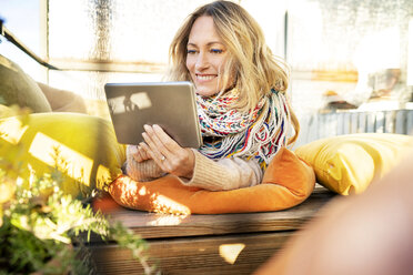Portrait of smiling blond mature woman relaxing in winter garden using digital tablet - DMOF00095