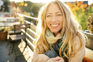 Portrait of happy blond mature woman on balcony in autumn - DMOF00098
