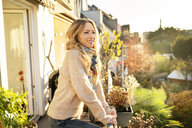 Portrait of smiling blond mature woman standing on balcony at autumn - DMOF00101