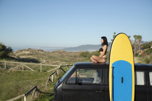 Spain, Andalusia, Tarifa, woman sitting on roof of a camper van stand up paddle board at the coast - KBF00389