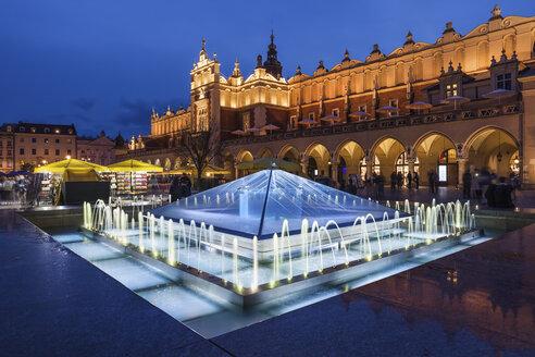 Poland, Krakow, Main Square in Old Town at night, illuminated fountain and Cloth Hall (Sukiennice), Renaissance style city landmark - ABOF00388