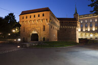 Poland, Krakow, Barbican fortification at night - ABOF00397