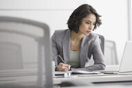 Businesswoman working at laptop in conference room - HEROF04155