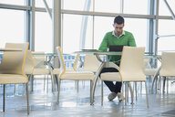 Businessman working at table in office cafeteria - HEROF04191