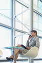 Businesswoman talking on cell phone in modern lobby - HEROF04215