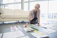 Creative businesswoman reviewing proofs in office - HEROF04335
