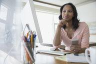 Pensive woman using computer at home - HEROF04416