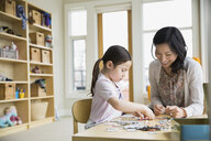Mother and daughter assembling jigsaw puzzle - HEROF04455