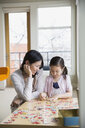 Mother and daughter assembling jigsaw puzzle - HEROF04458