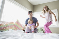 Father and daughters playing on bed - HEROF04572